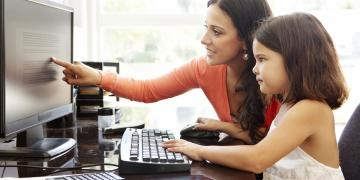 mother and daughter using the computer together