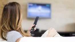 Woman with remote watching television on couch.