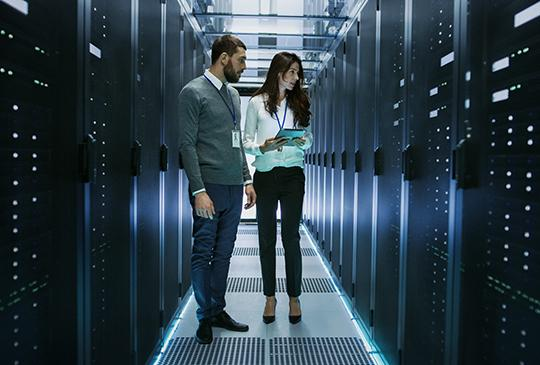 man and woman working in a server farm