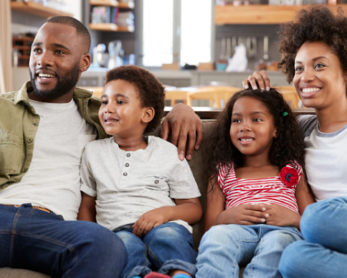 Young African American family watches TV on their couch.